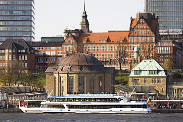 A tour boat docks by the St. Pauli Landing Stages (Landungsbruecken) while buildings of St. Pauli overlook the harbour in Hamburg, Germany, Europe