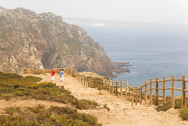 People walk along cliffs overlooking the Atlantic Ocean at Europe's most westerly point at Cabo da Roca, Portugal, Europe