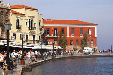 People walk by the waterfront restaurants and cafes within the Venetian harbour at Chania (Canea), Crete, Greek Islands, Greece, Europe