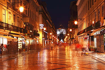 Warm summer's night on the cobbled Rua Augusta, leading to Arch of Rua Augusta, in the Baixa district of Lisbon, Portugal, Europe