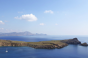 Rocky peninsulas of land poke into the Aegean Sea at Lindos, Rhodes, Dodecanese, Greek Islands, Greece, Europe