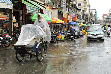Traffice, including a cyclo and taxi, on a waterlogged street during the monsoon season in Phnom Penh, Cambodia, Indochina, Southeast Asia, Asia