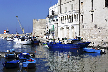 Blue wooden boats and fishing vessels in the walled harbour of Monopoli in Apulia, Italy, Europe
