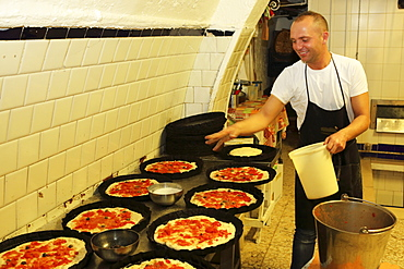 A baker at work making focaccia, a local delicacy, in a bakery in the Bari Vecchia quarter of Bari, Apulia, Italy, Europe