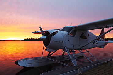 A float plane at the end of a jetty, at sunrise, in Egenolf Lake in northern Manitoba, Canada, North America
