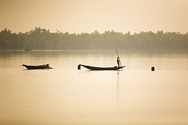 A man stands on a boat in the Sunderbans (Sundarbans) National Park, UNESCO World Heritage Site, West Bengal, India, Asia