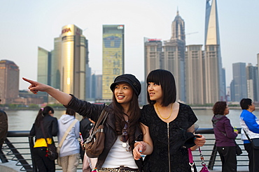 Tourists smiling and pointing, The Bund, Huangpu District, with Pudong District on the background, Shanghai, China, Asia