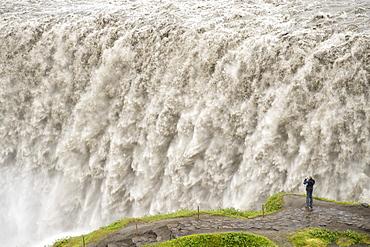 Tourist photographing Dettifoss waterfall near Myvatn in Vatnajokull National Park, northeast area, Iceland, Polar Regions