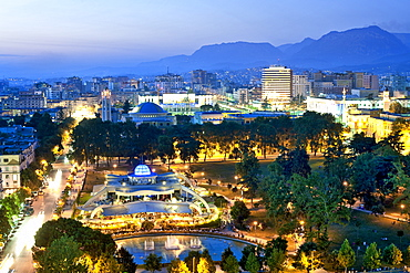 Dusk view of city with Rinia Park in the foreground, Tirana, Albania, Europe