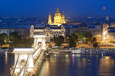 Full moon over city, with Szechenyi Chain Bridge and the dome of St. Stephen's Basilica, Budapest, Hungary, Europe