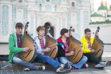Four young Ukrainian bandurists playing banduras and singing in front of St. Sophia's Cathedral in Kiev, Ukraine, Europe