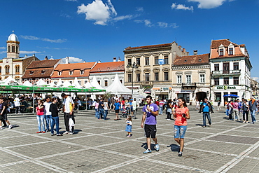 Buildings and pedestrians in Brasov Council Square in the old town in Brasov, a city in the Transylvania region of Romania, Europe