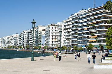 View of buildings on Nikis Avenue and pedestrians strolling on the waterfront in Thessaloniki, Greece, Europe
