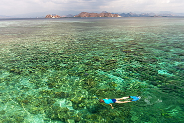 A tourist snorkeling in the waters off the western coast of Flores island, Indonesia.