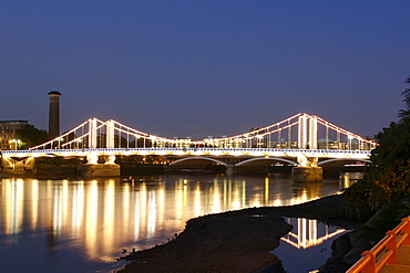 Dusk view of Chelsea Bridge and its lights reflecting in the Thames River in London.
