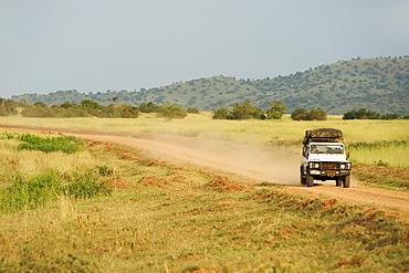Land Rover Defender driving through the Kabwoya Wildlife Reserve in western Uganda.