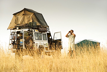 A man looking through binoculars alongside a Land Rover Defender at a campsite in the Kabwoya wildlife reserve in Uganda.