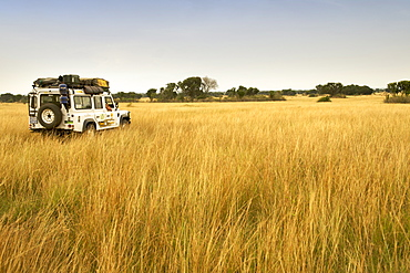 Land Rover Defender driving through the plains at Pelican Point in Queen Elizabeth National Park in western Uganda.