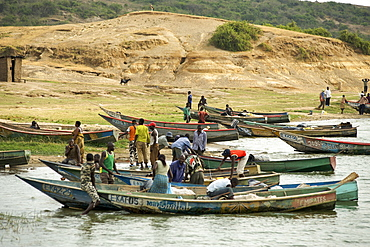 Ugandan villagers along the bank of the Kazinga channel that leads between Lake George and Lake Edward in the Queen Elizabeth National Park in western Uganda.