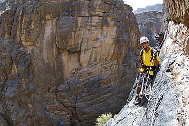 A man doing the Via Ferrata hike in Snake Canyon, part of Wadi Bani Auf in Jebel Akhdar of the western Hajar mountains in Oman.