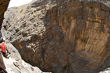 Hikers doing the Via Ferrata hike in Snake Canyon, part of Wadi Bani Auf in Jebel Akhdar of the western Hajar mountains in Oman.