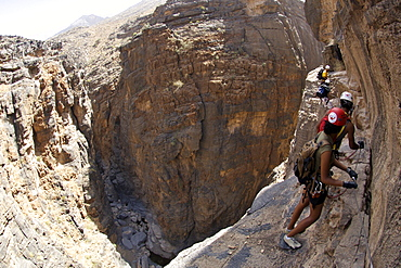 Hikers doing the Via Ferrata hike in Snake Canyon in Jebel Akhdar of the western Hajar mountains in Oman.