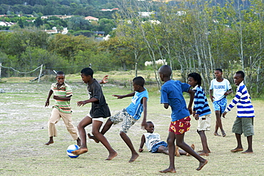 African children playing soccer barefoot in a field in Hout Bay in Cape Town, South Africa.