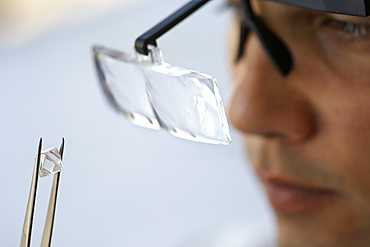An uncut diamond being examined during sorting at De Beers' Harry Oppenheimer House building in Kimberley South Africa.