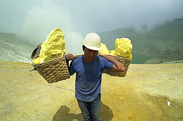 Miner on the crater rim of 2400m volcano of Gunung Ijen in east Java, Indonesia, Southeast Asia, Asia