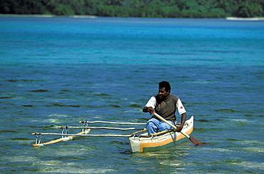 Man in outrigger canoe going to work on the small resort island of Erakor in Erakor Lagoonjust south of the capital, Efate Island, Port Vila, Vanuatu