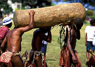 Men from the island of Pentecost carry a traditional tamtam, a slit drum hollowed from a tree trunk, at a Melanesian cultural festival, Efate Island, Port Vila, VanuatuVANUATU.  Port Vila.  Efate Island