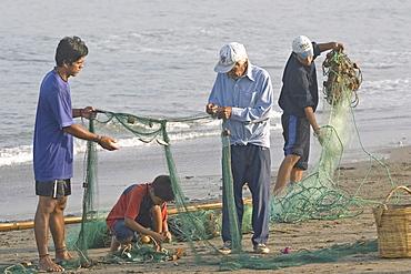 Fishing family on the beach at the popular far north coast fishing & surfing village of Huanchaco, near Trujillo, Peru, South America.