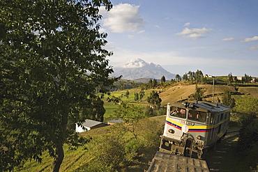 Bus and the famous El Nariz del Diablo (The Devil's Nose) train en route to Riobamba with Chimborazo volcano in the distance, Riobamba, Chimborazo Province, Central Highlands, Ecuador, South America