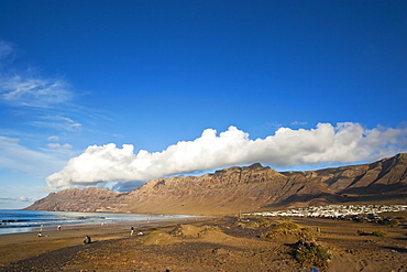 Spectacular 600m volcanic cliffs of the Risco de Famara rising over Lanzarote's finest beach at Famara, with its low-rise bungalow development, Famara, Lanzarote, Canary Islands, Spain, Atlantic Ocean, Europe - 83-12375