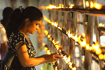 Devotee lighting candles at sunset in the Temple of the Sacred Tooth Relic (Temple of the Tooth), site of Buddhist pilgrimage, Kandy, Sri Lanka, Asia