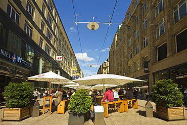 People sitting al fresco under parasols outside restaurant on pedestrianised shopping street, Spitalerstrasse, Hamburg, Germany, Europe