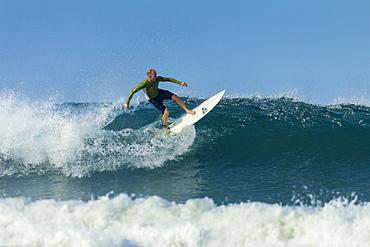 Surfer on shortboard riding wave at popular Playa Guiones surf beach, Nosara, Nicoya Peninsula, Guanacaste Province, Costa Rica, Central America