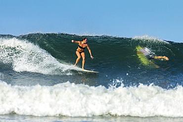 Girl surfer riding wave at popular Playa Guiones surf beach, Nosara, Nicoya Peninsula, Guanacaste Province, Costa Rica, Central America