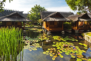 Traditional kampung style rooms over carp ponds at the Kampung Sumber Alam hot springs hotel, Garut, West Java, Java, Indonesia, Southeast Asia, Asia