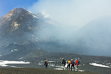 Hikers from the cablecar near the smoking summit of 3350m volcano Mount Etna during an active phase, Mount Etna, UNESCO World Heritage Site, Sicily, Italy, Mediterranean, Europe
