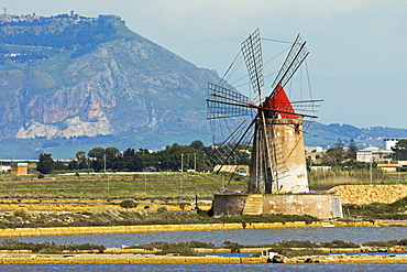 Windmill on Stagnone Lagoon in the salt pan area south of Trapani, with Mount Erice in the distance, Marsala, Sicily, Italy, Mediterranean, Europe