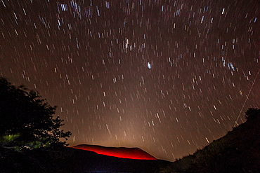 Glowing active volcanic crater of Volcan Telica at night with star trails and shooting star (meteor) on right, Leon, Nicaragua, Central America