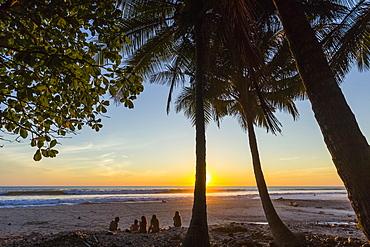 People by palm trees at sunset on Playa Hermosa beach, far south of the Nicoya Peninsula, Santa Teresa, Puntarenas, Costa Rica, Central America