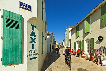 Cyclist on Rue Lamathe in the island's principal western town, Ars en Re, Ile de Re, Charente-Maritime, France, Europe