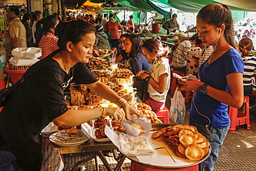 Girl wearing headphones buys food in the eating area of this huge old market, Central Market, city centre, Phnom Penh, Cambodia, Indochina, Southeast Asia, Asia