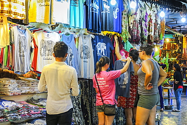 Girl tourists browse souvenir clothes in the Art Center Night Market in the centre of this NW tourist town, Siem Reap, Cambodia, Indochina, Southeast Asia, Asia