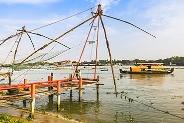 Old Chinese fishing nets and tour boat on the waterfront of Vypin Island with Fort Cochin beyond, Fort Vypin, Kochi, Kerala, India, Asia