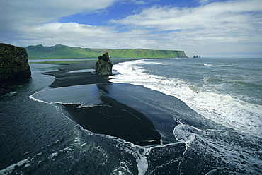 Black volcanic sand and sea stack at south coast bird sanctuary, Dyrholaey, Iceland, Polar Regions