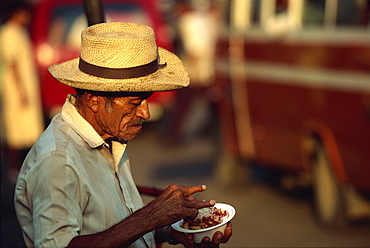 Portrait of an elderly man in a straw hat eating a snack in San Miguel, El Salvador, Central America
