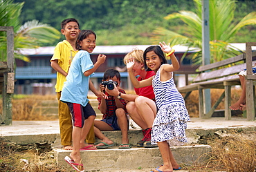 A group of Iban Dayak children with a tourist and camera outside their longhouse on the Rajang River near Kapit in Sarawak, northwest Borneo, Malaysia, Southeast Asia, Asia